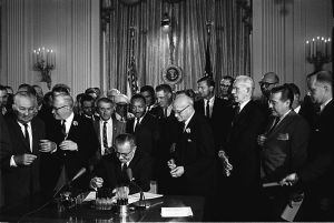 LBJ signs the Civil Rights Act of 1965 while Martin Luther King, Jr. looks on