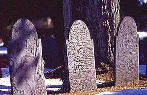 Weather-eroded slate stones in the old burial ground