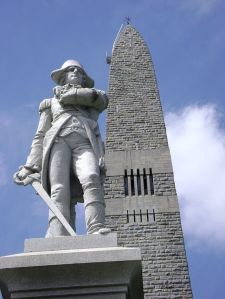 That's a statue of Vermont military leader Seth Warner erected in front of the Bennington obelisk (Credit: Wikipedia)